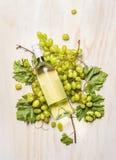 Raisins frais sur la branche avec les feuilles et la bouteille de vin blanc sur le fond en bois blanc, vue supérieure photos libres de droits