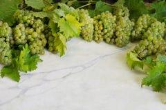 Raisins juteux savoureux verts mûrs frais sur la table de cuisine de marbre image libre de droits