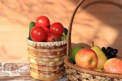 Raisins noirs juteux, pommes, poires, tomates dans un panier sur la table image libre de droits