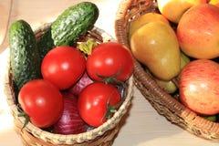 Raisins noirs juteux, pommes, poires, tomates dans un panier sur la table photo libre de droits
