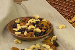 Raisins and nuts in a saucer on the background of canvas Royalty Free Stock Images