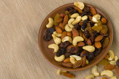 Raisins and nuts in a saucer on the background of canvas Stock Photo