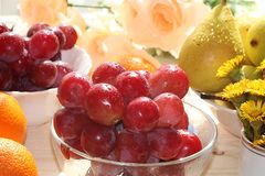 Raisins rouges, poires et oranges juteux sur un fond clair avec des baisses en gros plan, photo stock