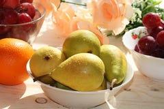 Raisins rouges, poires et oranges juteux sur un fond clair avec des baisses en gros plan, photographie stock