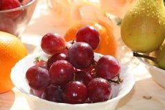 Raisins rouges, poires et oranges juteux sur un fond clair avec des baisses en gros plan, photos stock