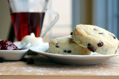 Raisins scones with raspberries jam. White cheeze and cup of tea Stock Images