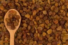 Raisins secs à la cuillère et à l'arrière-plan en bois des raisins secs Photos stock