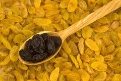 Raisins secs dans une cuillère en bois sur le fond de raisins secs Images stock