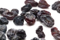 Raisins secs noirs sur un fond blanc Macro Photographie stock