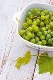 Raisins sur la table en bois blanche Images stock