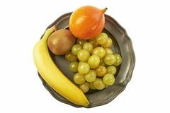 Raisins sur une plaque de métal, ainsi qu'une banane, des kiwis et un passiflore images stock
