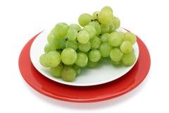 Raisins verts d'une plaque d'isolement avec le chemin Photos stock