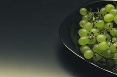 Raisins verts dans un plat noir Photos libres de droits