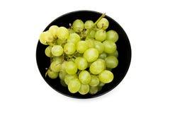 Raisins verts dans un plat noir sur un fond blanc photos stock