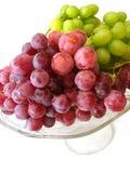 Raisins verts et rouges sur le plateau d'isolement Image stock