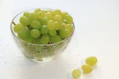Raisins verts juteux dans une tasse avec des baisses sur un plan rapproché humide lumineux de table, photos stock