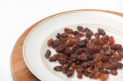 Raisins on the white plate on the kitchen wooden board Stock Images