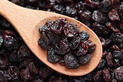 Raisins in a wooden spoon. On raisins background. Close-up Stock Photo