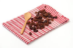 Raisins on the wooden spoon and kitchen tablecloth Stock Photography