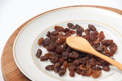 Raisins and wooden spoon on the white plate on the kitchen woode Royalty Free Stock Images