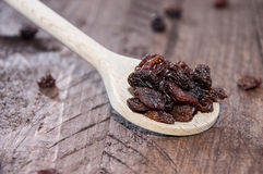 Raisins on a wooden spoon Stock Images