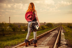 Raiway to horizon. Woman in jeans with guitar at countryside railway to horizon Stock Images