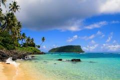 Raj wyspy tropikalna plaża w oceanie spokojnym z turkus wodą, złotym piaskiem i egzotycznymi drzewkami palmowymi, obrazy stock