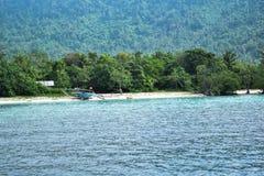 RAJABASA, BANDAR LAMPUNG, INDONESIA 3 LUGLIO 2018: Barca non identificata sulla riva nell'isola di Sebesi, Indonesia Fotografia Stock Libera da Diritti