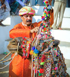 Rajasthani印地安人装饰他的骆驼在普斯赫卡尔市场,印度 库存照片