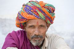 Rajasthani tribal man wearing traditional colorful turban attends the annual Pushkar Cattle Fair, Pushkar, Rajasthan, India. PUSHKAR, INDIA - OCTOBER 25, 2014 stock images