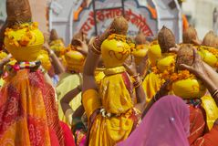 Rajasthani women wearing yellow and red sarees holding coconuts and pots take part in a religious procession in Bikaner, India. Bikaner, India, April 01, 2007 royalty free stock photo