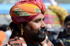 Rajput with bright turban and earring shows his moustache,Pushkar,India. PUSHKAR, INDIA - NOVEMBER 14: Unidentified rajput with bright turban and earring shows Royalty Free Stock Image