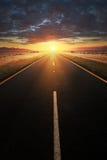 Rak asfaltväg som leder in i solljus Arkivbilder