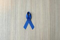 Rak Okrężnicy świadomość, zmrok - błękitny faborek na drewnianym tle dla wspierać ludzi żyć fotografia stock