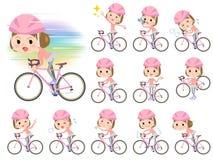 Raka kvinnor för kläder för smällhårrosa färger rider på den red cykeln Arkivbilder