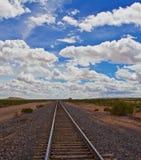 Raka spår till horisonten, molniga himlar Fotografering för Bildbyråer