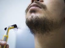 Rakapparat för guling för Closeupmanbruk som rakar det smutsiga skägget och mustaschen på hans framsida i badrum royaltyfria foton