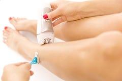 Rakapparat och epilator i hand för kvinna` s Elkraft vs manuell rakning Hårborttagningsalternativ och alternativ Royaltyfri Foto