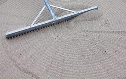 Rake making circles in sand Royalty Free Stock Image