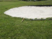 Rake near bunker on golf course royalty free stock photography