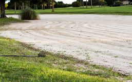 Rake next to golf course sand trap Stock Images