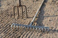 Rake and pitchfork on soil. Rake and pitchfork on loosened soil closeup Royalty Free Stock Photos