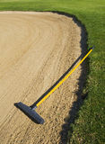 Rake in sand bunker. Gardening rake in the sand bunker of a golf course Stock Photography