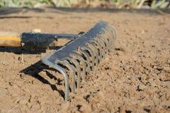 Rake on soil. Rake on loosened soil closeup. Shallow depth of field Royalty Free Stock Images