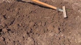 Rake soil in spring garden stock footage