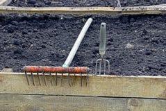 Rake on a wooden board and black earth garden Royalty Free Stock Photos