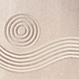 Raked sand patterns in Japanese Zen Garden. Wit simple flowing waves and concentric circles in a square frame format Stock Images
