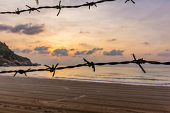 A raked sandy beach with barbed wire. An unknown raked sandy beach with barbed wire against refugees Royalty Free Stock Photography