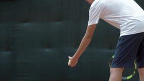Rakend tennisbal, werpt de professionele speler van het jongenstennis bal en slaat met een racket in lucht op hof stock video