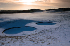 Rakes in bunkers at dawn on a snow covered course